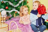 Little girl and boy sit on furry rug under christmas tree, boy holds red gift box, girl look at him poster