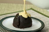 stock photo of custard  - dark chocolate sponge dessert with pouring custard - JPG