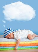 stock photo of yawning  - Yawning sleeping baby in funny hat with dream cloud for image or text - JPG