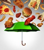 stock photo of  habits  - Bad diet protection food concept with a group of greasy fatty fast food falling down like rain and a green umbrella stopping the unhealthy food as a metaphor for poor nutrition and changing eating habits - JPG