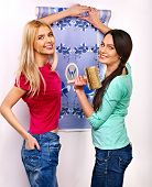 Happy women glues wallpaper at home.