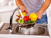 stock photo of saucepan  - Happy man washing fruit at kitchen - JPG