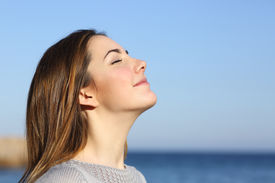 stock photo of breathing exercise  - Woman profile portrait breathing deep fresh air on the beach with the ocean in the background - JPG