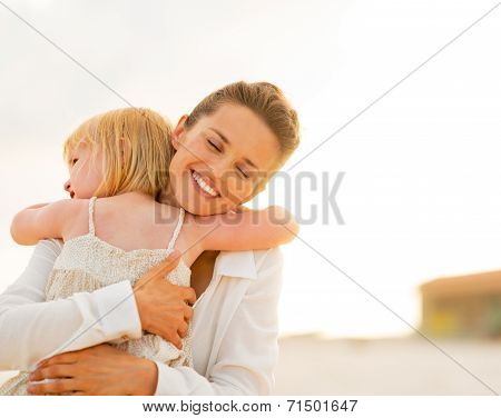 Portrait Of Mother And Baby Girl Hugging On The Beach In The Eve