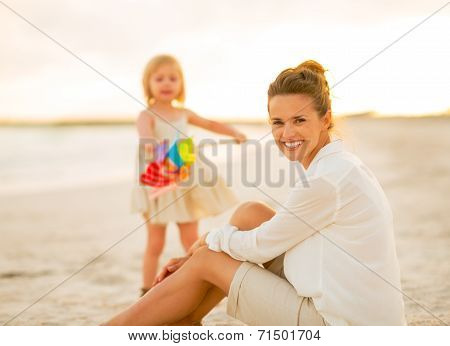 Mother And Baby Girl Spending Time On The Beach In The Evening
