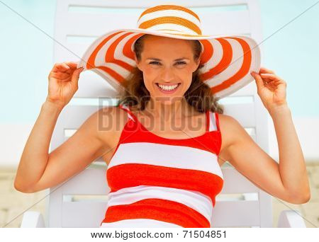 Portrait Of Smiling Young Woman In Hat Laying On Chaise-longue