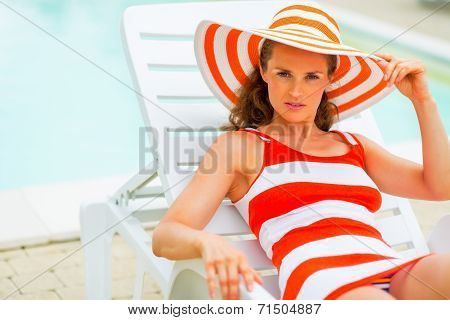Portrait Of Young Woman In Hat Laying On Chaise-longue