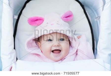 Sweet Smiling Baby Girl In A Bunny Hat Sitting In A White Stroller
