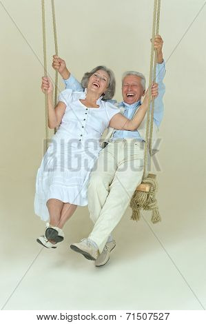 Beautiful elderly couple on swing