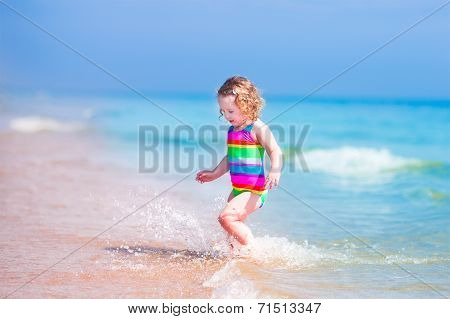 Happy laughing little girl in colorful rainbow bathing suit running and playing on ocean coast