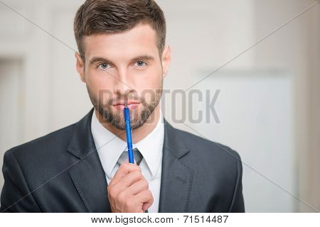 Portrait of handsome businessman in office interior touching his