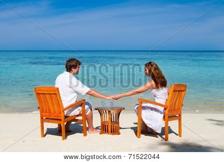 Young Beautiful Couple Enjoying Cocktails On A Tropical Beach