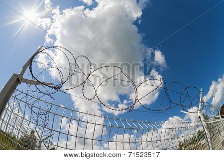 Fence With Barbed Wire On Blue Sky Background