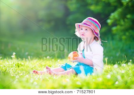 Toddler Girl Eating An Aple In The Garden
