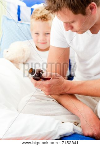 Concerned Man Looking After His Sick Son