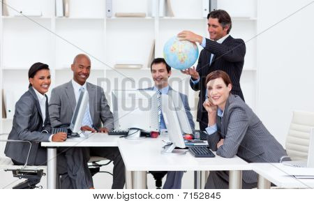 Smiling Manager Holding A Globe With His Team Working At Computers
