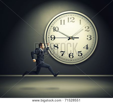 serious running businessman and big white clock in dark room