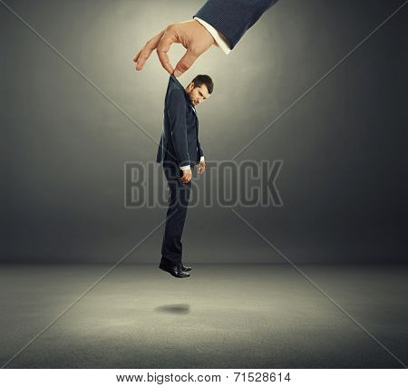 big hand holding small discontented businessman in dark room