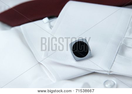 A pair of cuff links on a sleeve of the white shirt and a cravat near it