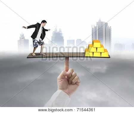 Businessman Stands On Finger Seesaw Vs Gold