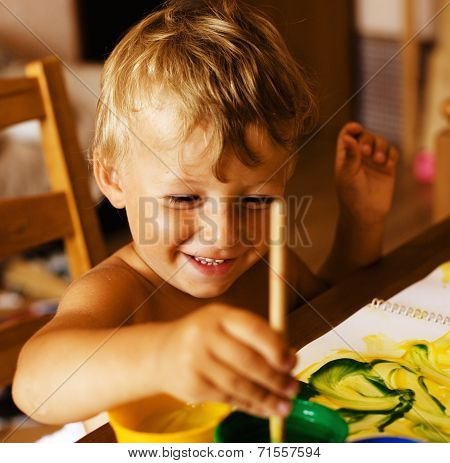 portrait of little cute boy painting at home interior