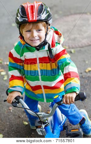 Adorable Kid Boy In Red Helmet And Colorful Raincoat Riding His First Bike
