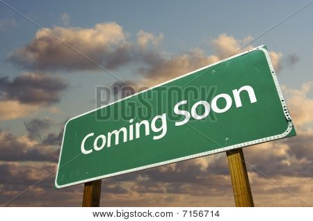 Coming Soon Green Road Sign Over Clouds