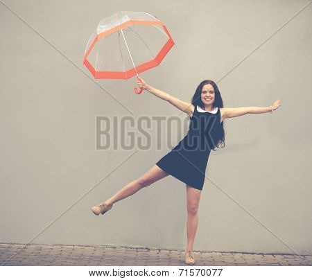 Beautiful Brunette With Long Hair In A Short Black Dress Jumping Under A Transparent Umbrella.colorf