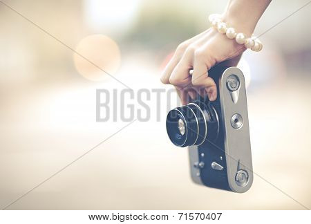 Beautiful Female Hand Hold The Camera Of Vintage Close Up. Colorful Hipster Photo