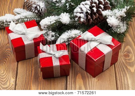 Christmas fir tree with snow and red gift boxes on rustic wooden board