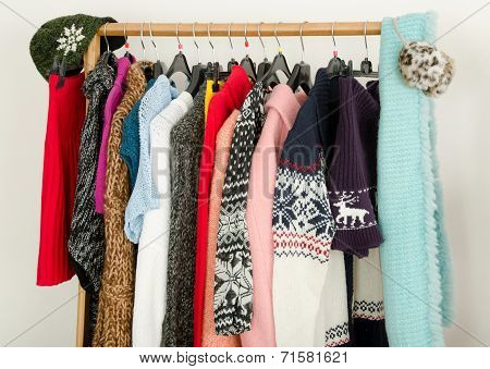Close up on wardrobe with winter clothes nicely arranged.