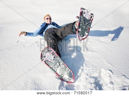 a woman playing in the snow with snow shoes on