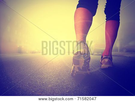 an athletic pair of legs jogging or running on pavement during sunrise or sunset - healthy lifestyle concept toned with a retro vintage instagram filter effect