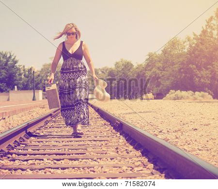 a girl walking down train tracks with a suitcase and hat done with a vintage retro like instagram filter