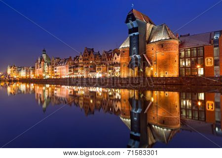 GDANSK, POLAND - 14 JANUARY 2014: Medieval port crane over Motlawa river at night. This port crane built between 1442 and 1444 is the symbol of Gdansk and the oldest surviving port crane in Europe.