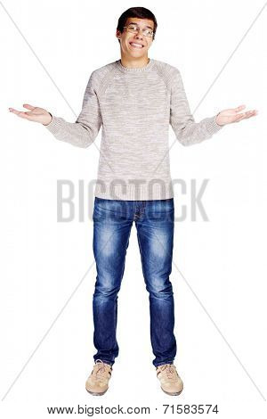 Full length portrait of confused young man in glasses and beige sweater making helpless gesture isolated on white background