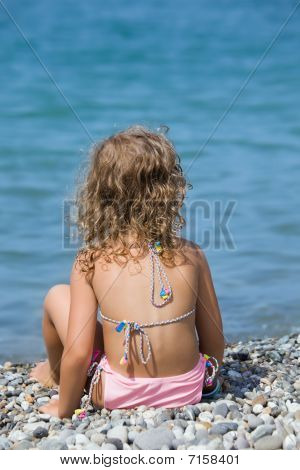 Pretty Little Girl Sitting On Stone Seacoas, Sitting By Back