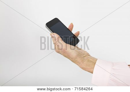 Businesswoman's hand holding smart phone in office