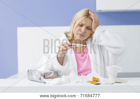 Young woman suffering from cold checking tempereature