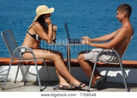 Man and woman sitting at table under open sky on background of sea.