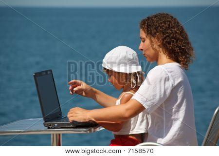 Mãe e filha sentado no computador portátil. Dia de verão ensolarado em abrir o céu no fundo do mar.