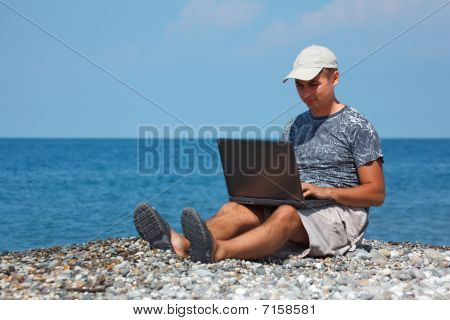 Man in cap sitting on beach with laptop on his knees against backdrop of sea.