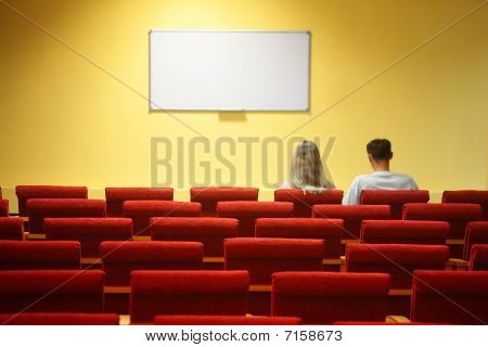 empty conference hall. rows of a chairs. man and woman sitting in chairs