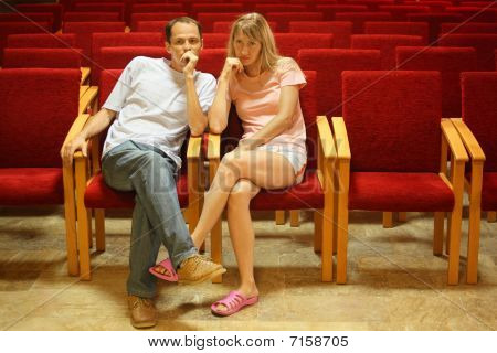 man and woman sitting on a chairs in empty presentation hall.