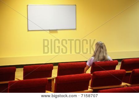 woman sitting in a chair in a first row of empty presentation hall