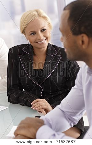 Attractive young businesswoman chatting with businessman, smiling happy.
