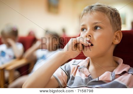 Boy Sitting In Cinema Armchair, Holding Fingers Near Mouth