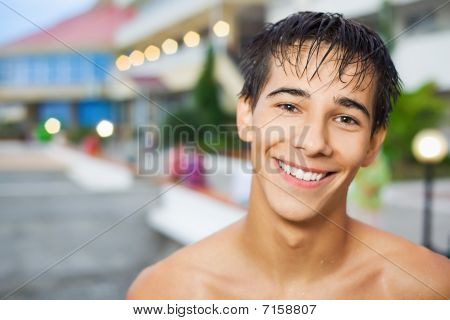 Smiling Teenager Boy Standing Near Hotel On Resort In Evening