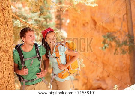 Hiking - young couple of hikers relaxing resting in Bryce Canyon walking smiling happy together. Multiracial couple, young Asian woman and Caucasian man in Bryce Canyon National Park landscape, Utah