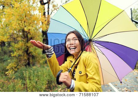 Fall / Autumn concept - woman excited under rain with umbrella. Beautiful young female wearing raincoat surprised and excited in the rain. Mixed race Asian Caucasian girl in her 20s walking in forest.